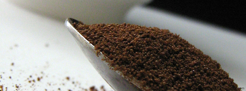 Spoon of grinded coffee on table Facebook cover photo